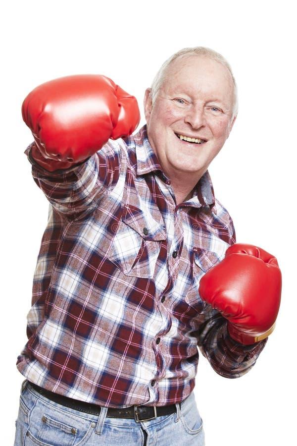 Starszy mężczyzna jest ubranym bokserskich rękawiczek ono uśmiecha się zdjęcie stock