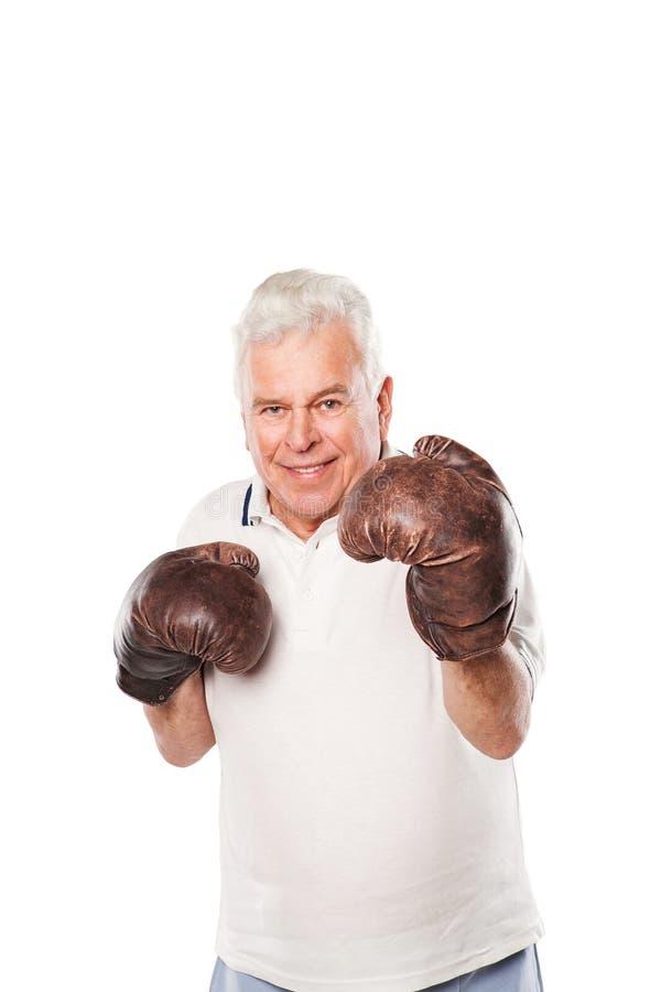 Starszy mężczyzna jest ubranym bokserskie rękawiczki ono uśmiecha się na bielu obrazy stock