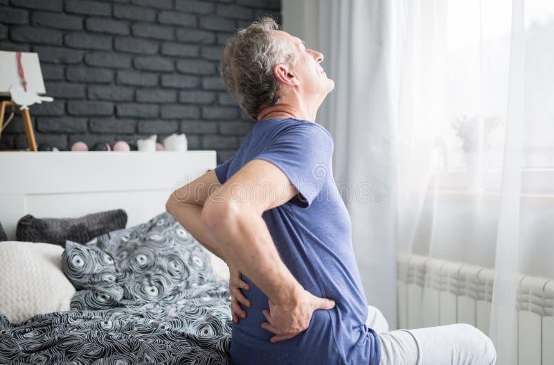 Starszy mężczyzna jest usytuowanym na łóżku z niskim bólem pleców obrazy royalty free