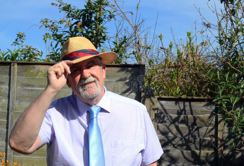 Starszy mężczyzna mówi dobrego dzień z słomianym kapeluszem fotografia royalty free