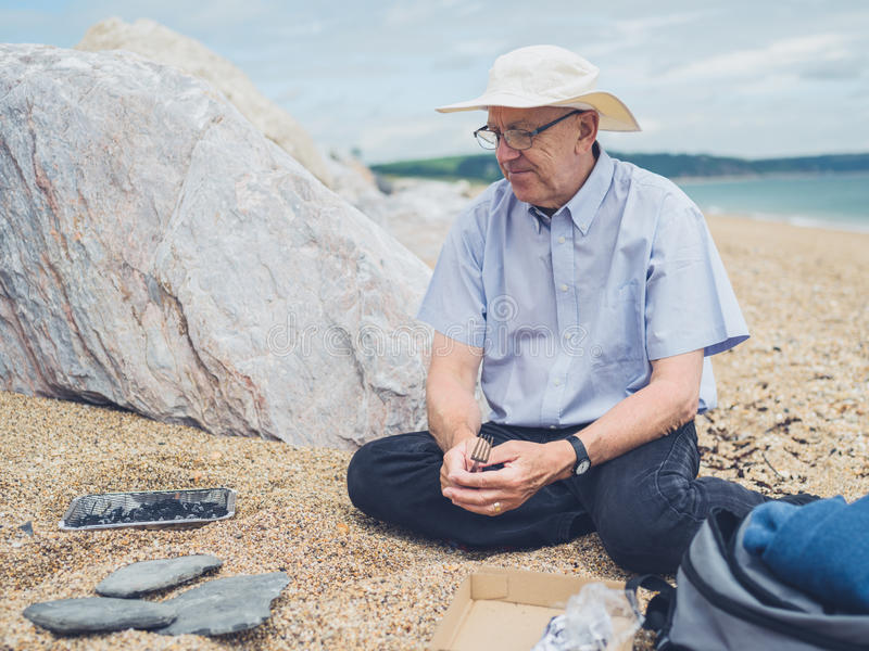 Starszy mężczyzna ma grilla na plaży obrazy royalty free