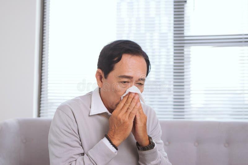 Starszy mężczyzna ma grypę, z papierowym wytarciem dmucha jego nos fotografia royalty free