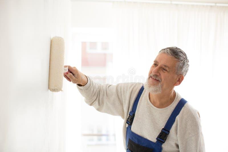 Starszy mężczyzna maluje ścianę w jego do domu fotografia stock