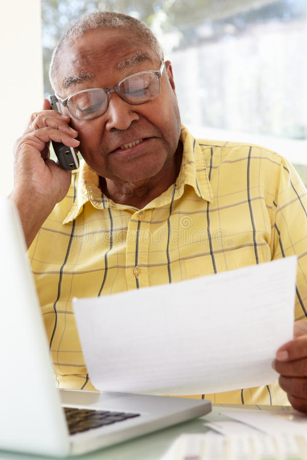 Starszy mężczyzna Na telefonie Używać laptop W Domu obraz royalty free