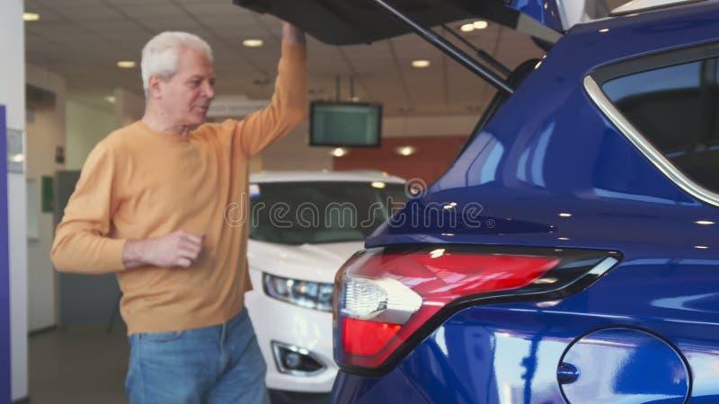 Starszy mężczyzna otwiera samochodowego bagażnika przy przedstawicielstwem handlowym zdjęcia royalty free
