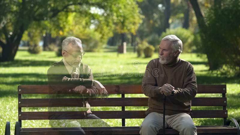 Starszy mężczyzna patrzeje pustą ławkę i pamięta jego przyjaciela, strata, wspominki zdjęcie royalty free