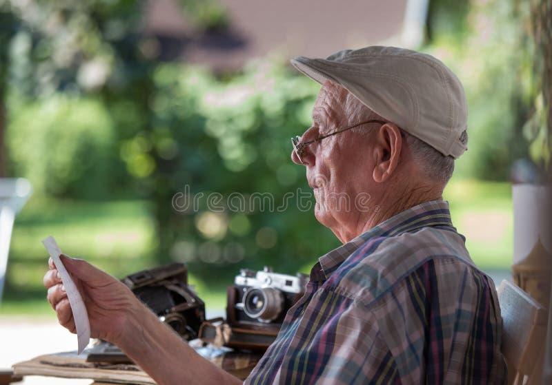 Starszy mężczyzna patrzeje stare fotografie zdjęcia stock