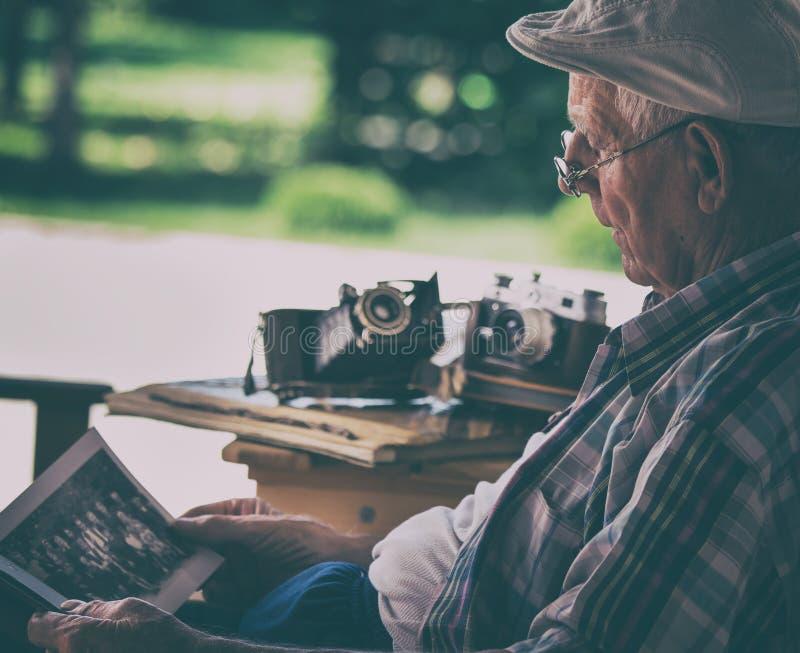 Starszy mężczyzna patrzeje stare fotografie fotografia royalty free