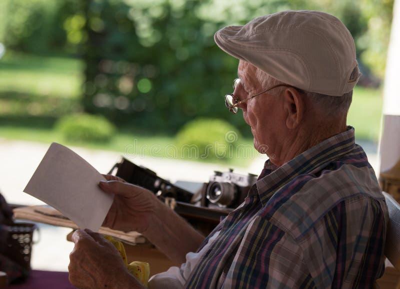 Starszy mężczyzna patrzeje stare fotografie obrazy royalty free