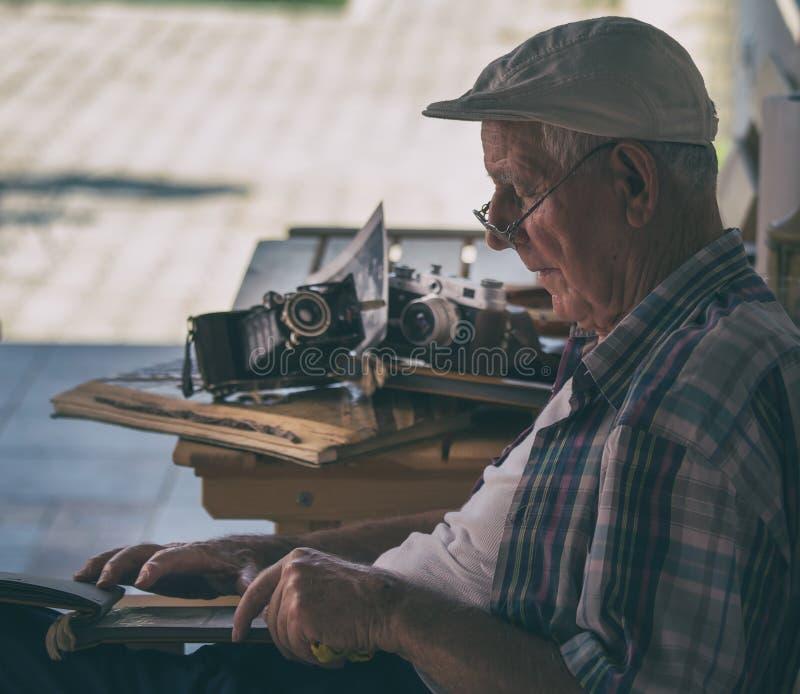 Starszy mężczyzna patrzeje stare fotografie zdjęcia royalty free