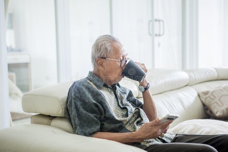 Starszy mężczyzna pije gorącej herbaty na leżance fotografia royalty free