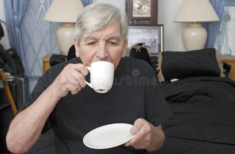 Starszy mężczyzna pije od filiżanki fotografia stock