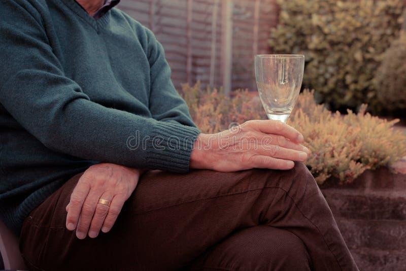 Starszy mężczyzna pije wino w ogródzie zdjęcia royalty free