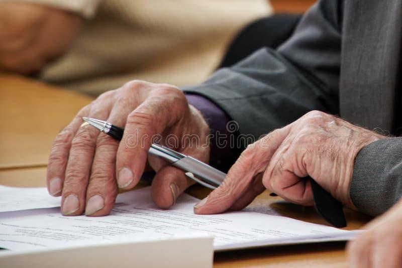 Starszy mężczyzna pisze piórze w kwestionariuszu Starość i uczenie Bezrobocie i emerytura fotografia royalty free