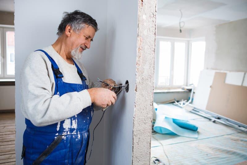 Starszy mężczyzna pracuje na elektrycznych instalacjach zdjęcia stock