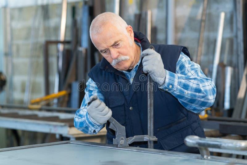 Starszy mężczyzna pracuje przy manufactory zdjęcie royalty free