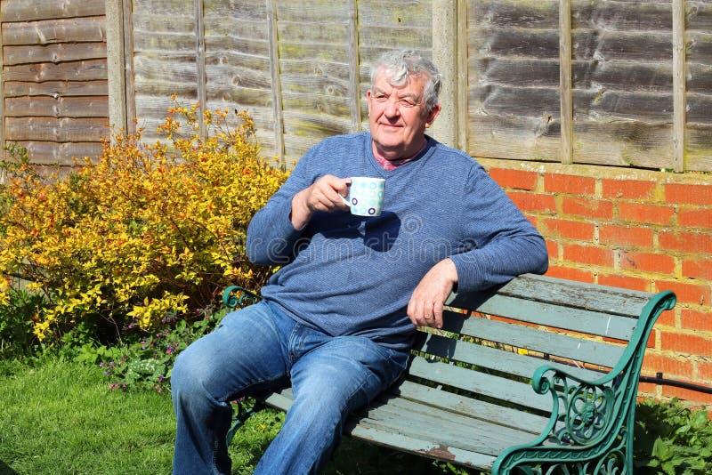 Starszy mężczyzna relaksuje pijący kawę w ogródzie fotografia stock