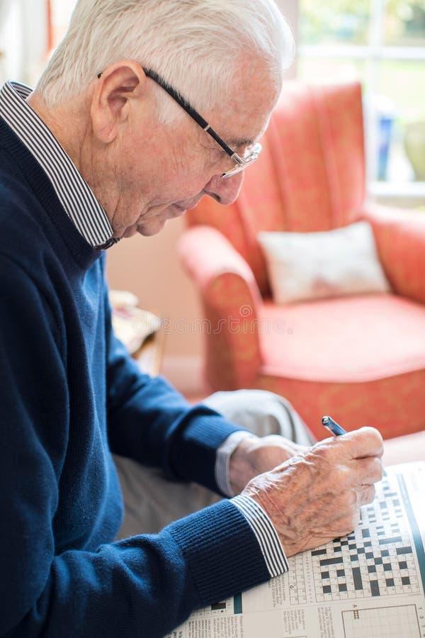 Starszy mężczyzna Robi Crossword łamigłówce W Domu obrazy royalty free