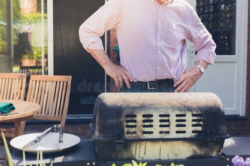 Starszy mężczyzna robi grillowi w ogródzie zdjęcia stock