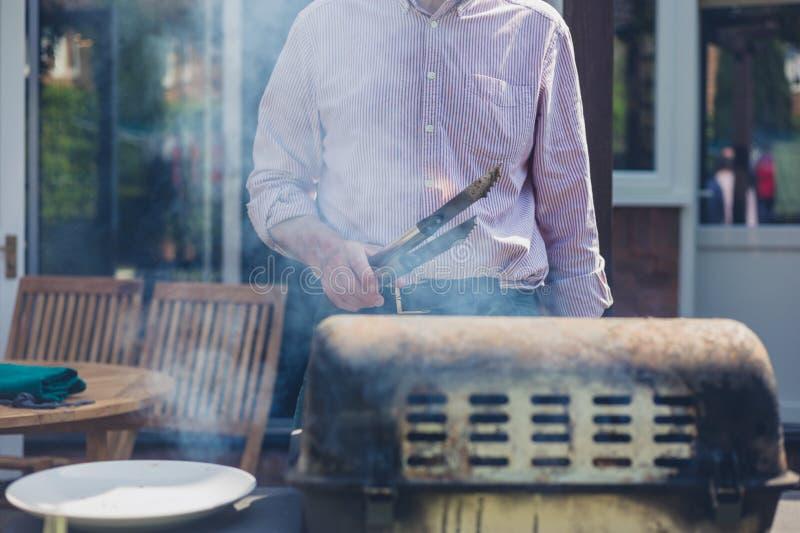 Starszy mężczyzna robi grillowi w ogródzie obraz stock