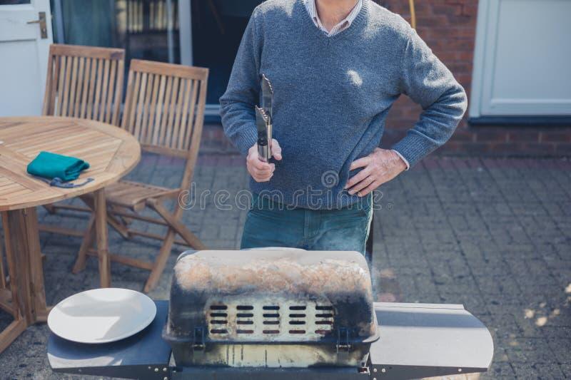 Starszy mężczyzna robi grillowi w ogródzie zdjęcie stock