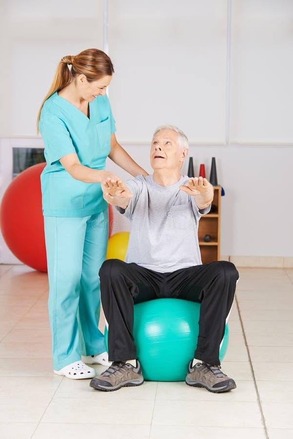 Starszy mężczyzna robi sprawności fizycznej ćwiczeniu w fizjoterapii zdjęcia royalty free