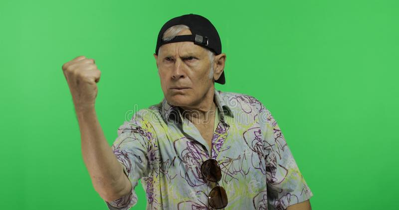 Starszy mężczyzna rusza się z jego ręki pięścią turysta kłóci się przy someone groźnie zdjęcie stock