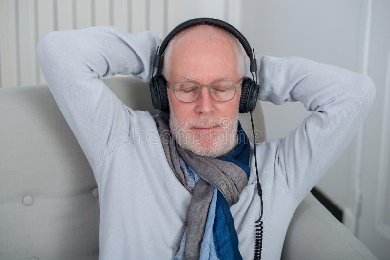 Starszy mężczyzna słucha muzyka w domu w hełmofonach fotografia stock