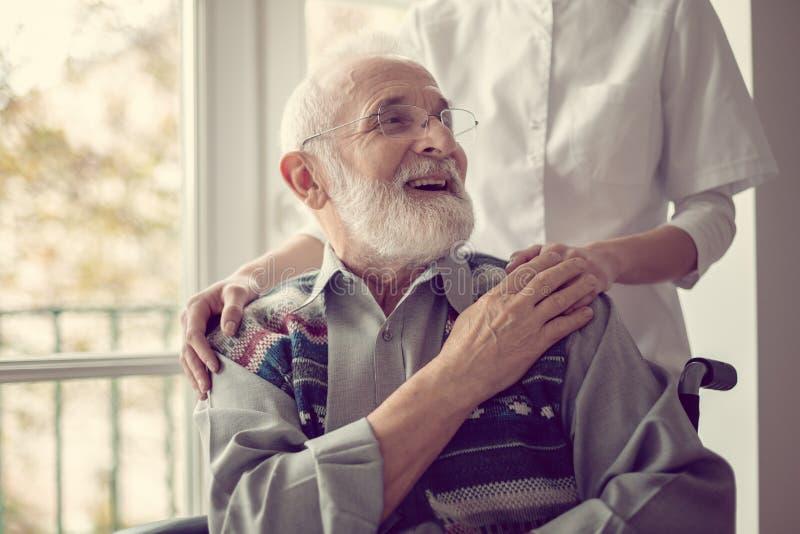 Starszy mężczyzna siedzący na wózku inwalidzkim, śmiejący się i trzymający rękę pielęgniarki fotografia royalty free
