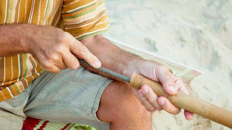 Starszy mężczyzna siedzi na plaży i robić rękami flet, w górę zdjęcia stock