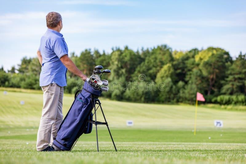 Starszy mężczyzna stoi dumnie na kiju golfowym obraz royalty free