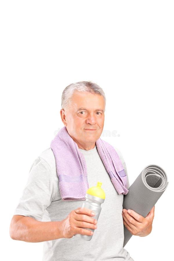 Starszy mężczyzna trzyma bidon i ćwiczenie matujemy zdjęcia royalty free