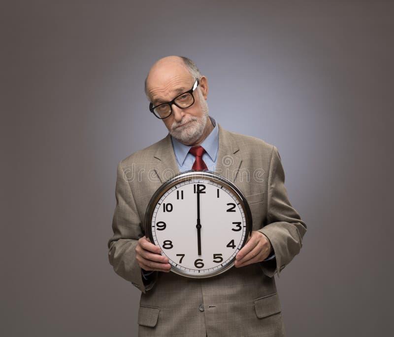 Starszy mężczyzna trzyma dużego ściennego zegar zdjęcia stock