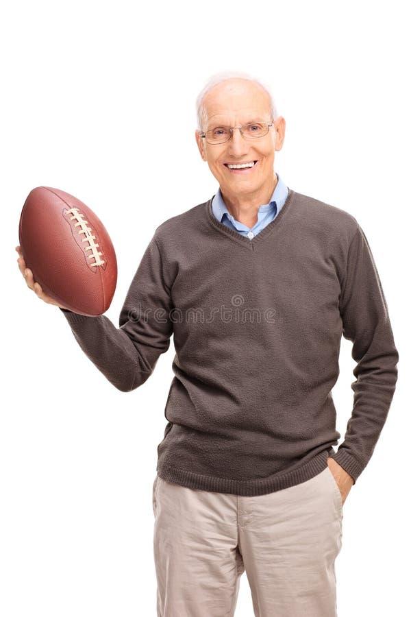 Starszy mężczyzna trzyma futbol amerykańskiego obraz stock