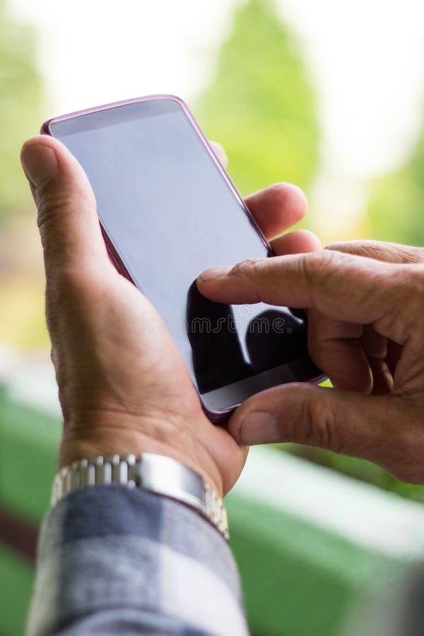 Starszy mężczyzna używa mądrze telefon obraz royalty free