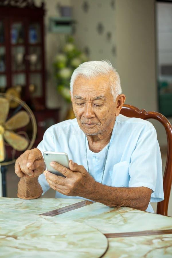 Starszy mężczyzna używa telefon komórkowego w domu obraz royalty free