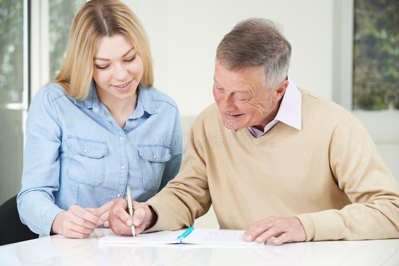 Starszy mężczyzna Uzupełnia Sudoku liczby łamigłówkę Z Nastoletnim zdjęcia stock