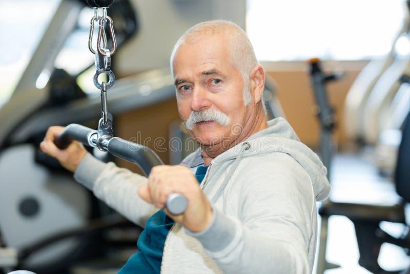 Starszy mężczyzna w gym pracującym z ciężarami out zdjęcie stock