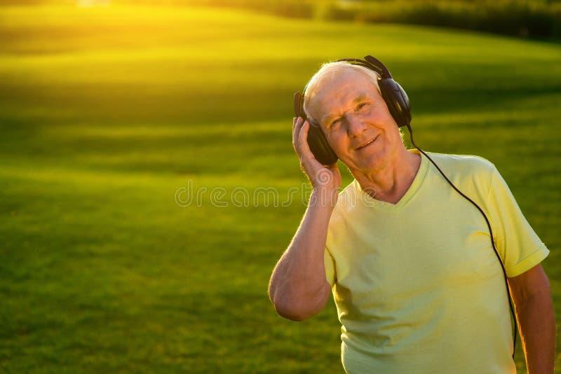 Starszy mężczyzna w hełmofonach obraz royalty free