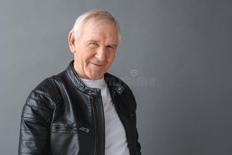 Starszy mężczyzna w skórzanej kurtki pozycji odizolowywającej na szarej przyglądającej kamerze figlarnie w górę obraz stock