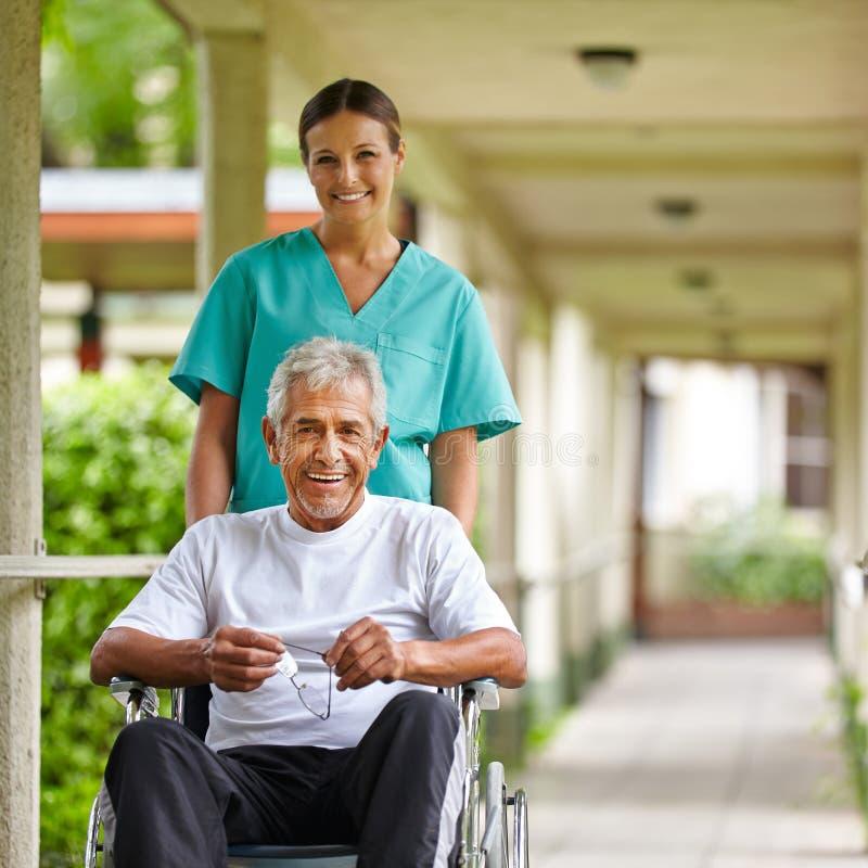 Starszy mężczyzna w wózek inwalidzki z pielęgniarką obraz stock