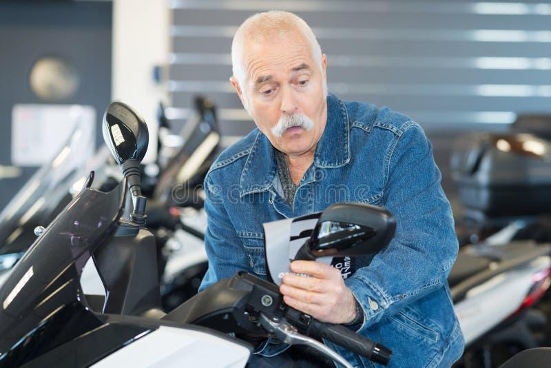Starszy mężczyzna wybierający motocykl do kupienia obraz stock