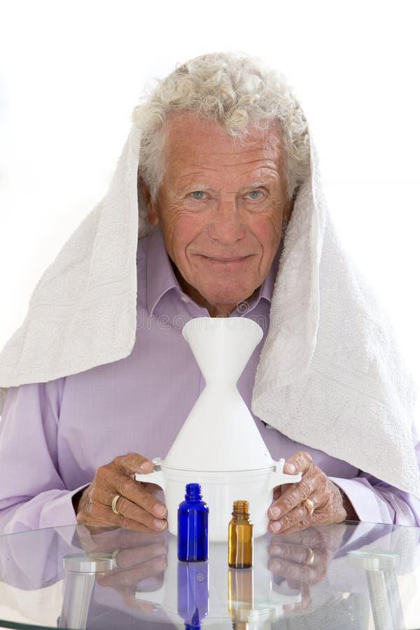 STARSZY mężczyzna Z grypą PRZYGOTOWYWA inhalację fotografia royalty free