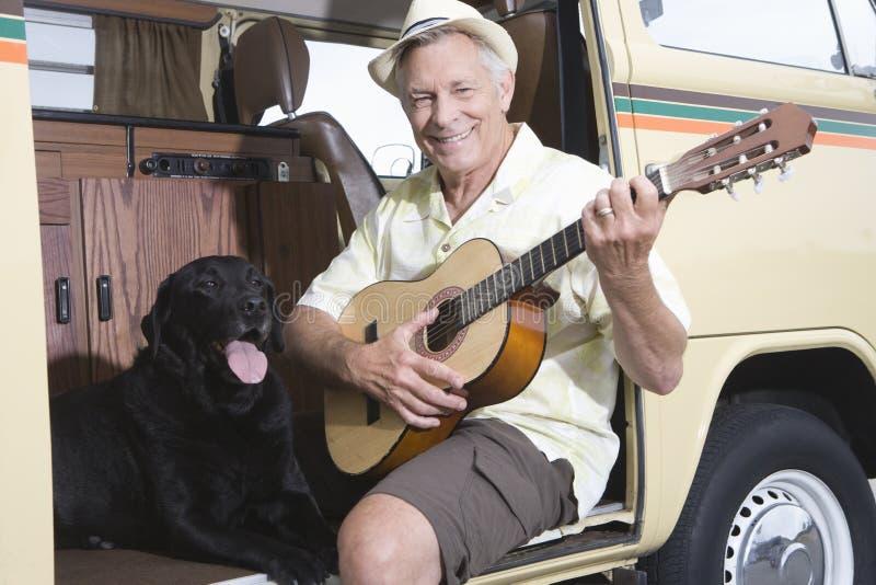 Starszy mężczyzna Z Jego Psią Bawić się gitarą W Campervan zdjęcie royalty free