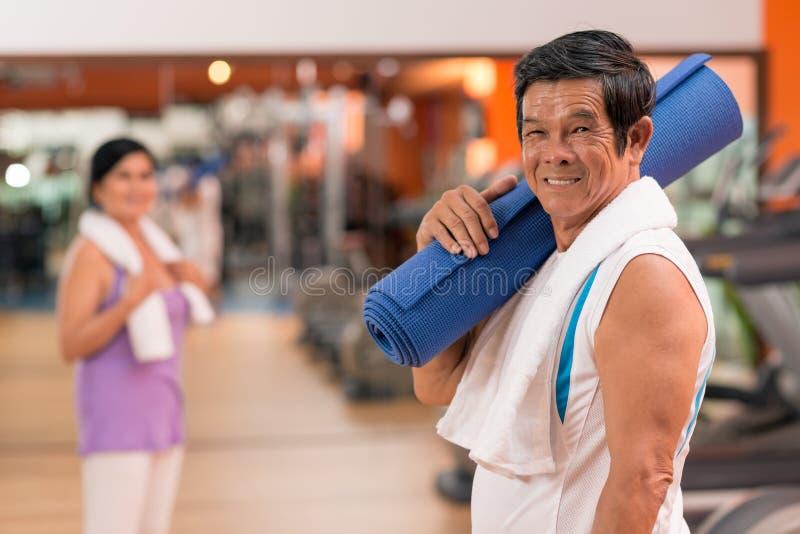 Starszy mężczyzna z joga matą obraz royalty free