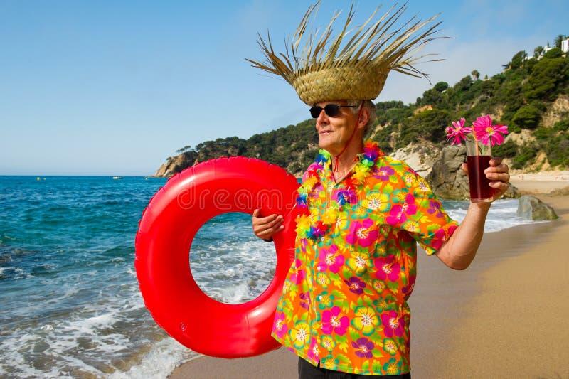Starszy mężczyzna z koktajlu napojem przy plażą zdjęcie stock