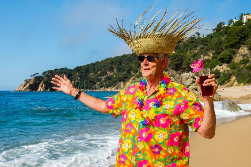 Starszy mężczyzna z koktajlu napojem przy plażą obraz stock