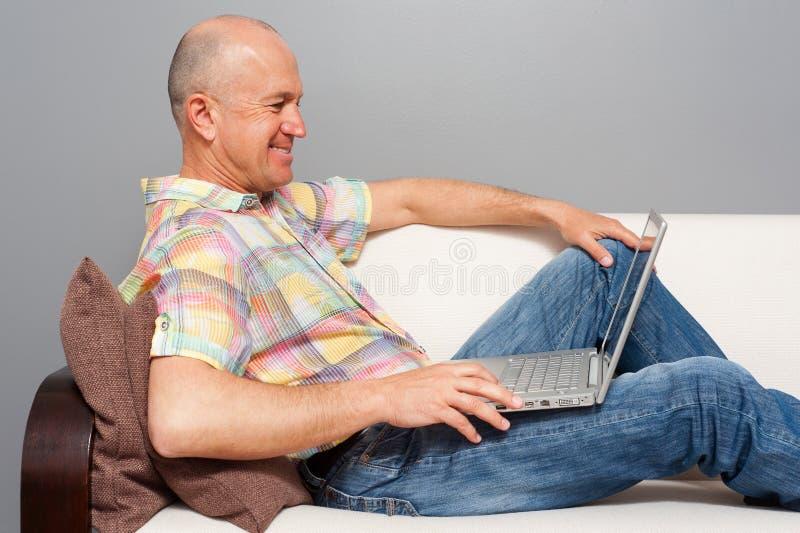 Starszy mężczyzna z notatnika lying on the beach na kanapie w domu zdjęcia stock