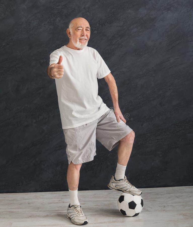 Starszy mężczyzna z piłki nożnej piłką pokazuje kciuk up zdjęcia royalty free