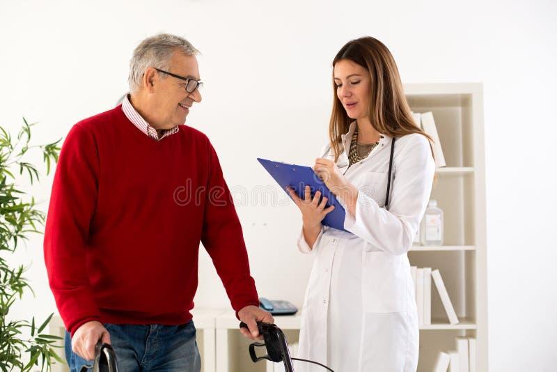 Starszy mężczyzna z piechurem na konsultaci z lekarką zdjęcia stock